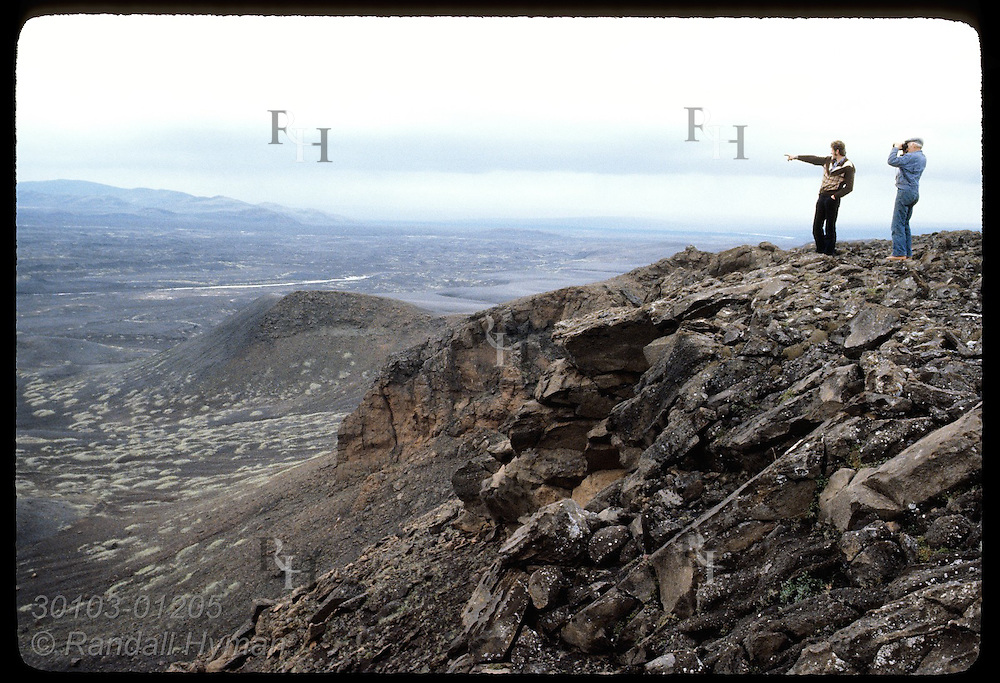 Two farmers stand on ridge surveying cinder-buried pastures one day after 1980 Hekla eruption. Iceland