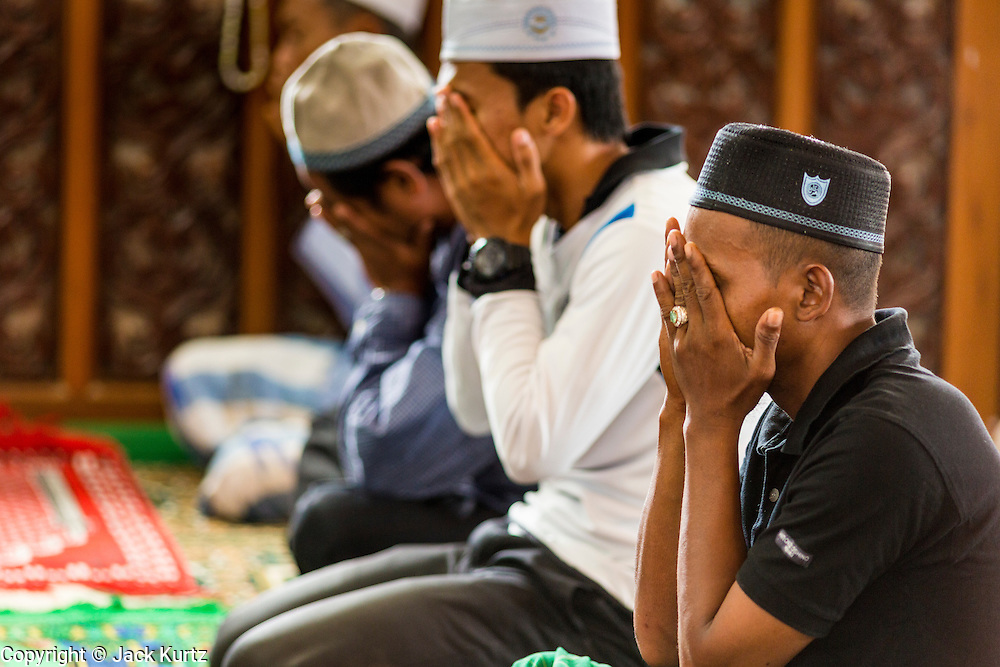 10 JULY 2013 - PATTANI, PATTANI, THAILAND:  Muslim men pray in Krue Se Mosque near Pattani, Thailand, during Ramadan.  Ramadan is the ninth month of the Islamic calendar, and the month in which Muslims believe the Quran was revealed. Muslims believe that the Quran was sent down during this month, thus being prepared for gradual revelation by Jibraeel (Gabriel) to the prophet Muhammad.  The month is spent fasting during the daylight hours from dawn to sunset. Fasting during the month of Ramadan is one of the Five Pillars of Islam.     PHOTO BY JACK KURTZ