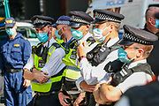 Police form a line as Extinction Rebellion Youth Cambridge blocked the road outside Baringa Partners building in London on Thursday, Sept 10, 2020 - in an attempt to highlight the involvement of Schlumberger Limited in what they call 'ecocide'. Schlumberger is an oilfield services company working in more than 120 countries and has four principal executive offices located in Paris, Houston, London, and The Hague. An article at the Guardian suggests that it's ubiquitous in fossil fuel operations across the world, has more staff than Google, turns over more than Goldman Sachs, and is worth more than McDonald's – yet you won't have heard of it. XR Youth of Cambridge said that the British government gave 'Schlumberger' a no-strings-attached £150 million bailout loan as it was laying off a fifth of its global workforce. Another activist added: 'Schlumberger is hiding in plain sight here in Westminster. Every day, hundreds of people walk past this building with no idea that they're on the doorstep of a climate crime scene.'<br /> Environmental nonviolent activists group Extinction Rebellion enters its 10th and final day of continuous ten days protests to disrupt political institutions throughout peaceful actions swarming central London into a standoff, demanding that central government obeys and delivers Climate Emergency bill. (VXP Photo/ Vudi Xhymshiti)