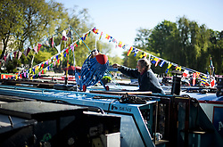 © Licensed to London News Pictures. 05/05/2018. London, UK. A boat owner makes adjustments to a mascot in the early morning sunshine as the Canalway Cavalcade festival takes place in Little Venice, West London on Saturday,  May 5th 2018. Inland Waterways Association's annual gathering of canal boats brings around 130 decorated boats together in Little Venice's canals on May bank holiday weekend. Photo credit: Ben Cawthra/LNP
