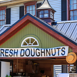 Intercourse, PA - June 18, 2016: Fresh doughnuts sign on a snack shack with Amish straw hats on display.