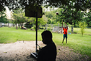 """LOWNDES COUNTY, AL – JULY 10, 2017: Deandrew, 13, plays basketball barefoot in the backyard where sewage from a nearby lagoons often spills over and contaminates the property. His aunt, Steviana, (right) said he's not supposed to play without shoes. """"Sometimes the stench is so bad, we can't go outside,"""" Steviana said. """"It's like we're prisoners in our own home."""" Along with roughly one in three individuals tested in a recent study conducted by Baylor, Deandrew tested positive for hookworm.<br /> <br /> A recent study conducted by Baylor University suggests that nearly one 1 in 3 people in Lowndes County have hookworm, a parasite normally found in poor, developing countries. Below ground septic tanks are common in Lowndes, but due to the chalky clay soil throughout much of the Black Belt, septic tanks are prone to backing up into people's homes during heavy rains. With failing or absent municipal sewage systems in the county, many families choose to live with open, above ground sewer systems made from PVC pipe, which pump raw sewage into nearby streams or open land."""