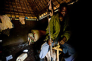 A member of an arrow boy group outside of Yambio sits with a hand made gun inside his home.