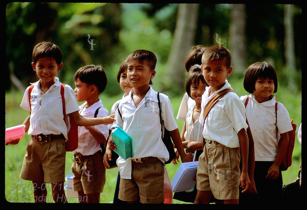 Schoolkids with bookbags clutch lunchboxes as they walk home in afternoon near Surat Thani. Thailand