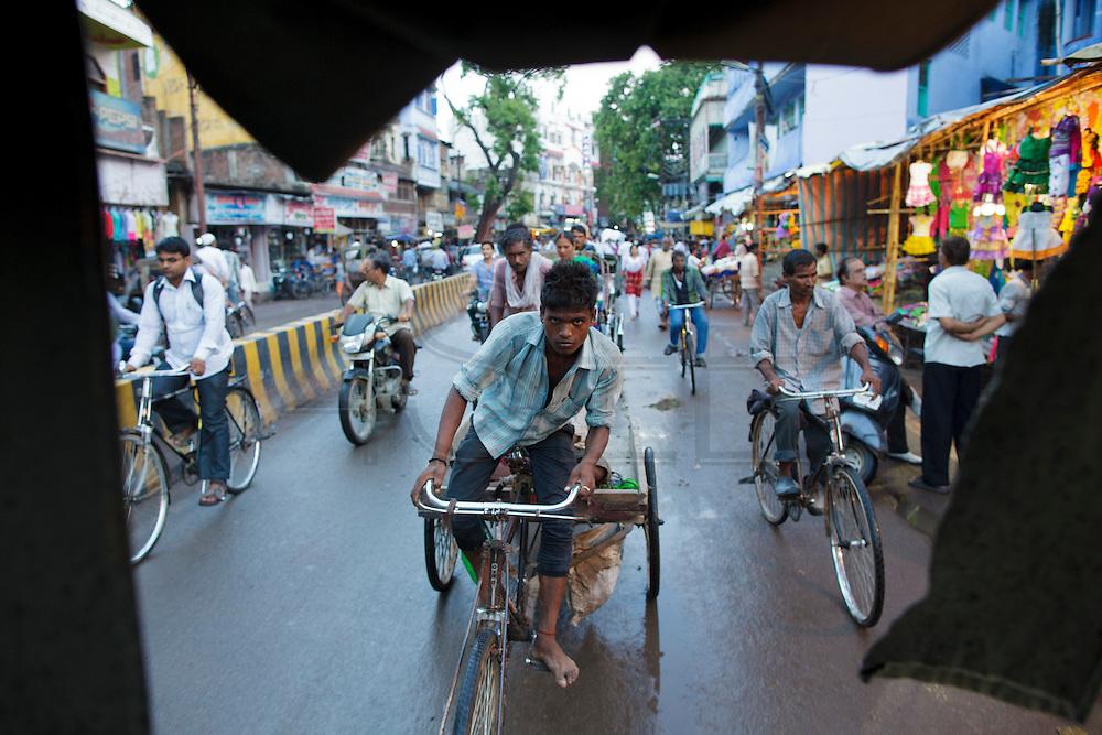 A rickshaw young driver portrayed form the back of anothe rickshaw at Varanasi in India.