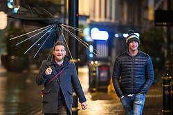 © Licensed to London News Pictures . 18/03/2017 . Cardiff , UK. A man carries an umbrella from which the fabric has been ripped from the spokes , in the wind . Revellers on a windy and wet Saint Patrick's Day night out in Cardiff city Centre . Photo credit: Joel Goodman/LNP