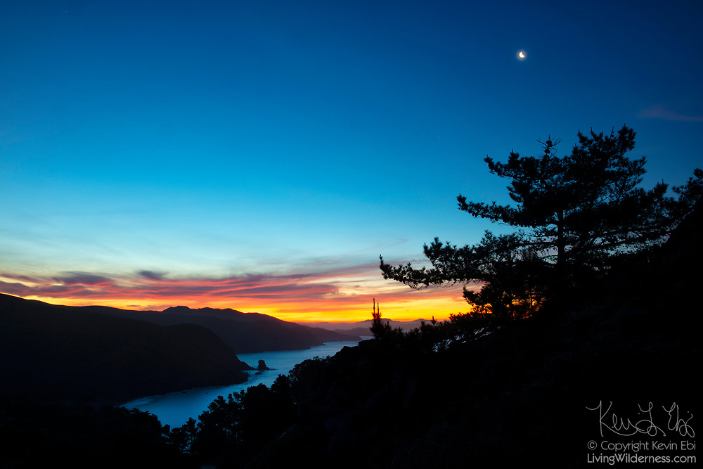 Clouds, turned fiery red by the rising sun, and the crescent moon are in the sky over Muir Beach in the Golden Gate National Recreation Area near San Francisco, California. This scene was captured from the Muir Beach Overlook trail.