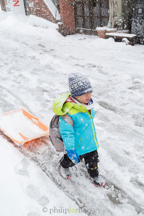 Child going with slide through snow, Nozawaonsen, Japan