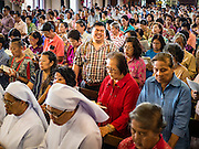 18 SEPTEMBER 2016 - BANGKOK, THAILAND:  Nuns and parishioners pray during the 100th anniversary mass for the sanctuary at Santa Cruz Catholic Church. Santa Cruz Church was establised in 1769 to serve Portuguese soldiers in the employ of King Taksin, who reestablished the Siamese (Thai) empire after the Burmese sacked the ancient Siamese capital of Ayutthaya. The church was one of the first Catholic churches in Bangkok and is one of the most historic Catholic churches in Thailand. The first sanctuary was a simple wood and thatch structure and burned down in the 1800s. The church is in its third sanctuary and was designed in a Renaissance / Neo-Classical style. It was consecrated in September, 1916. The church, located on the Chao Phraya River, serves as a landmark for central Bangkok.      PHOTO BY JACK KURTZ