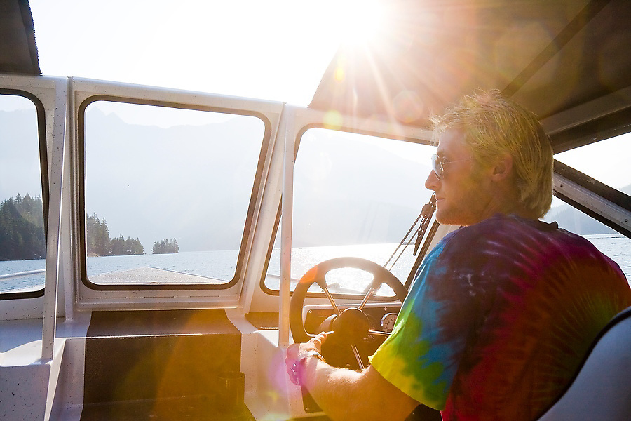An employee of the Ross Lake Resort drives the water taxi up Ross Lake to drop off climbers at Little Beaver Trailhead, access to the remote Northern Pickets Range in North Cascades National Park, Washington.
