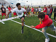 A member of the Waltrip High School football team tries to get by a member of the Wounded Warrior Amputee Football Team before a game against NFL Alumni, at Delmar Stadium, February 1, 2017.