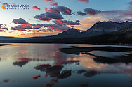 Red sunrise clouds over St Mary Lake and Divide Mountain in Glacier National Park, Montana, USA