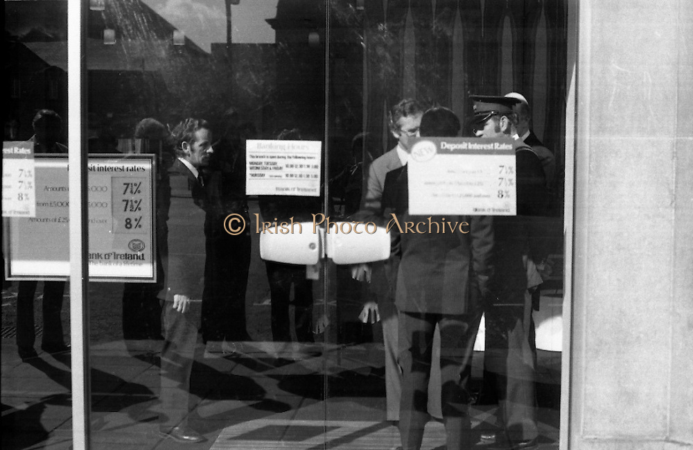 Fergus Rowan sits in at Bank of Ireland.  (J70)..1975..22.08.1975..08.22.1975..22nd August 1975..As a result of the 1970 bank strike which lasted for six months, the Rowan family business found itself in financial difficulties. During the strike the Rowans had had to accept cheques in good faith in order to stay in business. When the cheques came for settlement the bank refused as they stated that some were 'dodgy'. This put severe strain on the business which was eventually put into receivership.As part of the process the Rowan business beside the bank was put up for sale and was purchased by B.o I. Rowan was outraged and started a campaign against the bank which culminated in a sit in at the banks headquarters in Westmoreland St,Dublin. He also became a thorn in the side of the bank at the A.G.Ms raising many points...Image taken at the door of B.o.I. headquarters as officials and security staff decide what to do during the three day sit in of Fergus Rowan.