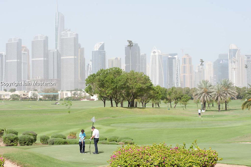 People playing golf on private golf course with skyline of Dubai in distance in United Arab Emirates, UAE