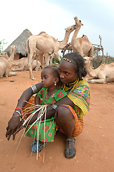 """Aifa sits with her niece Soudi as her family prepares breakfast and coffee before she heads to the market to receive a donkey from the womens union """"Hamada""""   in her village of Gulul, near Barentu, Eritrea.    (Photo by Ami Vitale)"""