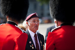 © Licensed to London News Pictures. 11/07/2013. London, UK. A British veteran of the Korean War talks to guardsmen on Horse Guards Parade in London today (11/07/2013) during preperations to march to Westminster Abbey. The parade and service held to commemorate the 60th Anniversary of the end of the Korean War, often known as the 'Forgotten War', which saw a United Nations force of many nations fight against North Korean and Chinese forces trying to invade South Korea. Photo credit: Matt Cetti-Roberts/LNP
