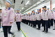 Employees march of the line towards the assembly area after row call at a Pegatron Corp. factory in Shanghai, China, on Friday, April 15, 2016. This is the realm in which the worlds most profitable smartphones are made, part of Apple Inc.s closely guarded supply chain.