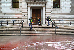 © Licensed to London News Pictures. 03/10/2019. London, UK. Workers clean up red dyed water which stains the entrance to The Treasury in Westminster after it had been sprayed by Extinction Rebellion activists. The stunt, which partly went wrong, was intended to cover the building in red dye looking like blood. Photo credit: Peter Macdiarmid/LNP