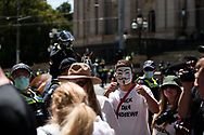 a man wearing a Guy Fawkes mask is seen during the Melbourne Freedom Rally at Parliament House. Police move into position on the steps of state parliament ahead of a planed protest. The groups who have organised the many Freedom Day protests over the last 3 months, attempted to march on State Parliament during Melbourne Cup Day demanding the sacking of Premier Daniel Andrews for the lockdown and attacks on their civil liberties. Police met with the protester's with significant force despite the city having had zero cases for five days. (Photo by Dave Hewison/Speed Media)