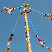While one performer plays a pipe instrument while standing on top, performers recreating a traditional Mayan ceremony of swinging from a tall pole suspended only by ropes at Xcarat Maya theme park south of Cancun and Playa del Carmen on Mexico's Yucatana Peninsula.