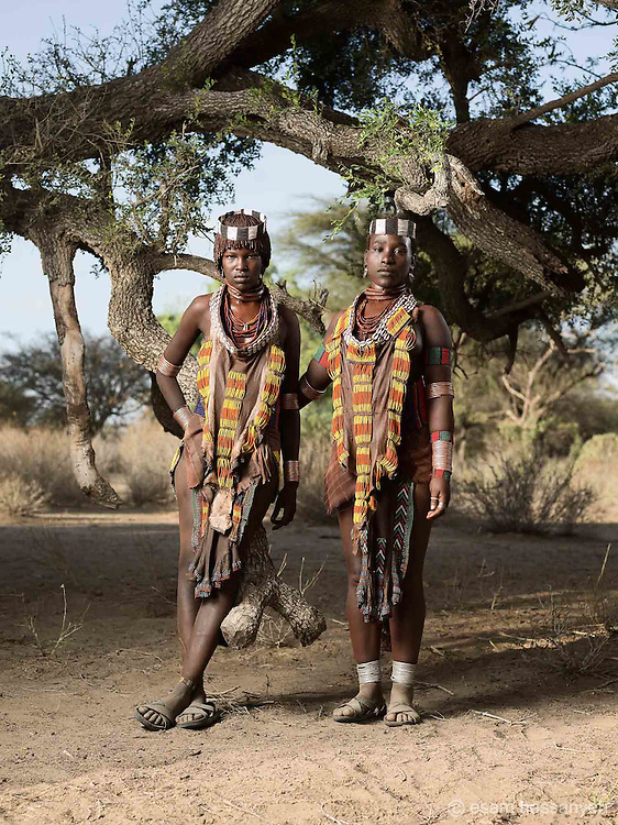 Dobo Wordo and Balo Daina wearing traditional Hamer daily dress.<br /> <br /> Both woman are married and are the first wives (Hamer men can have up to 3 wives).<br /> <br /> The first wife will wear 3 rings around her neck.  The lower 2 rings are plain bands but the top ring has a distinctive protruding shaped cylinder head.<br /> <br /> Here both Dobo and Balo wear a 3rd ring made of Dik Dik skin. This is a small antelope type animal that is common in the area. The skin of the Dik Dik is used as a temporary ring until the husband can afford the 3rd metal ring. This is much more expensive than the 2 plain rings as it is more difficult to make.<br /> <br /> The woman were from another village but would come daily to our location to visit.