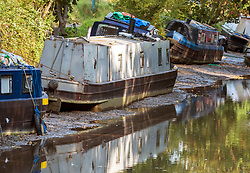 © Licensed to London News Pictures; 16/09/2020; Bath, UK. Canal going boats are seen grounded in the mud on the river Avon in Bath. Canal boats were evacuated and some boats sunk on the river Avon at Twerton after the sluice gates failed yesterday evening (15 September) and the water level dropped dramatically. The Fire Service assisted. The Canal and River Trust have issued a statement saying a drop in water level on the River Avon was caused by a failure of the Environment Agency's sluice gates and that the sudden and dramatic drop in levels meant that it was impossible to give warning to the boaters. The Canal and River Trust say they understand the difficulties faced by the EA in repairing the sluice and this is the second time this has happened, so they are looking to the EA to find a solution as a matter of urgency.  Photo credit: Simon Chapman/LNP.