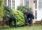 © Licensed to London News Pictures. 27/11/2014. Fetcham, UK. Officers carry out a search of the local area. A manhunt is under way across two counties after a man and woman were found stabbed to death in Surrey. The bodies were found at a house in Fetcham, near Leatherhead, after Surrey Police were alerted in the early hours.. Photo credit : Stephen Simpson/LNP