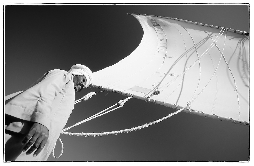 Nubian directing his felucca boat's sail, Aswan, Egypt