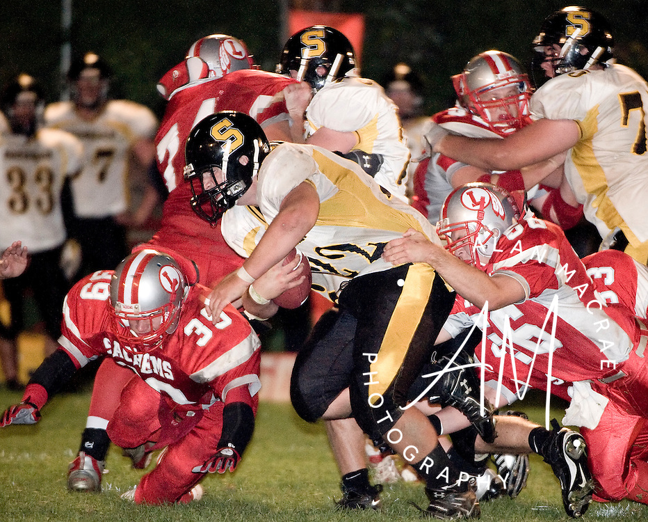 Souhegan's Steven Jellison is dragged down by Laconia's Joshua Cherok during Friday's clash at Laconia High School.  (Alan MacRae/for the Citizen)