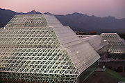 Biosphere 2 Project buildings at dawn with men working on the glass glazing. The Biosphere was a privately funded experiment, designed to investigate the way in which humans interact with a small self-sufficient ecological environment, and to look at possibilities for future planetary colonization.  1990