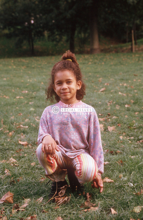 Portrait of young girl in park smiling,