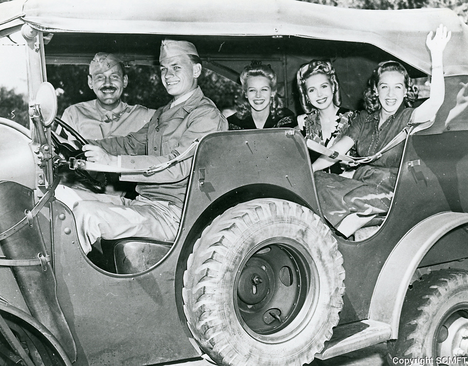 1943 Bonita Granville (Right) and Ann Miller (second from right) pose with servicemen in a Jeep, outside the Hollywood Canteen.