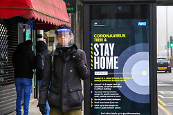 © Licensed to London News Pictures. 28/12/2020. London, UK. A man wearing a visor in north London walks past the government's 'Coronavirus Tier 4 - Stay Home'' publicity campaign poster. A new COVID-19 mutation has been discovered in the UK and many parts of the country came under Tier 4 restrictions on Boxing Day. The Medicines and Healthcare Products Regulatory Agency (MHRA) is likely to approve a COVID-19 vaccine developed by Oxford University and AstraZeneca this week. Photo credit: Dinendra Haria/LNP