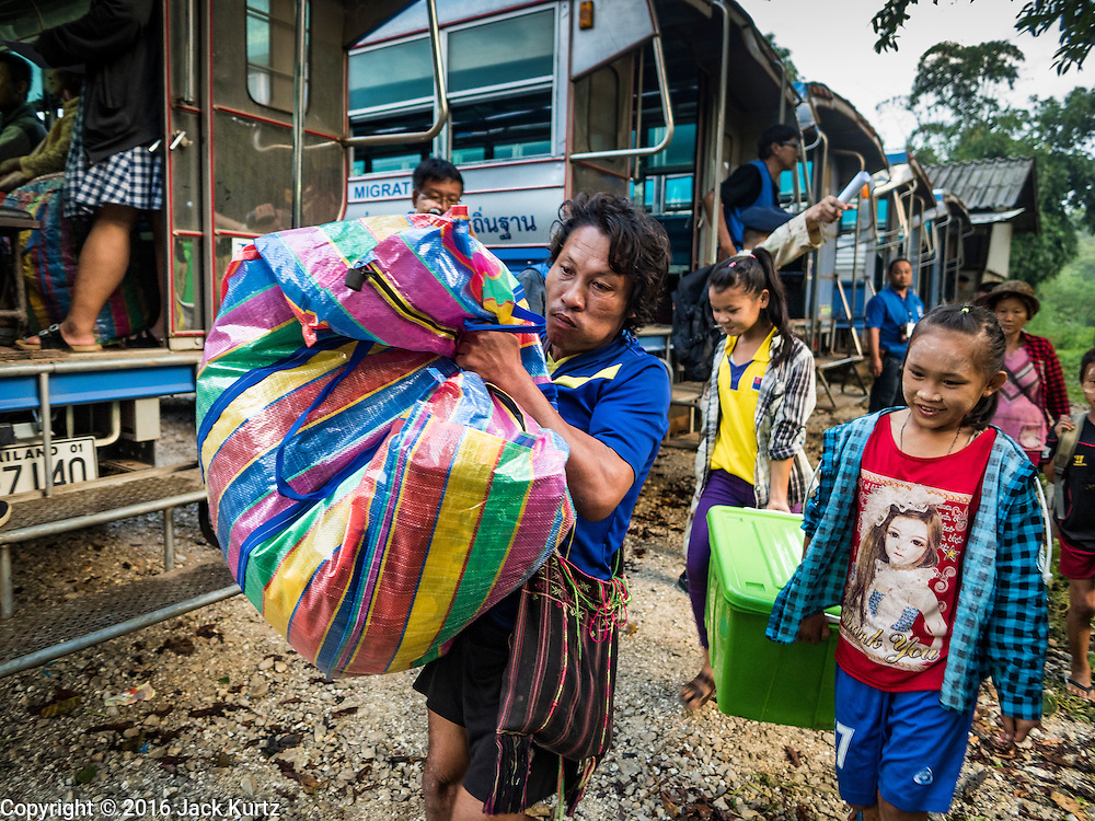 26 OCTOBER 2016 - NUPO TEMPORARY SHELTER, MAE CHAN, TAK, THAILAND:  Burmese refugees in the Nupo Temporary Shelter refugee camp walk to waiting buses before their repatriation Wednesday. Sixtyfive Burmese refugees living in the Nupo Temporary Shelter refugee camp in Tak Province of Thailand were voluntarily repatriated to Myanmar. About 11,000 people live in the camp. The repatriation was the first large scale repatriation of Myanmar refugees living in Thailand. Government officials on both sides of the Thai / Myanmar border said the repatriation was made possible by recent democratic reforms in Myanmar. There are approximately 150,000 Burmese refugees living in camps along the Thai / Myanmar border. The Thai government has expressed interest several times in the last two years in starting the process of repatriating the refugees.    PHOTO BY JACK KURTZ