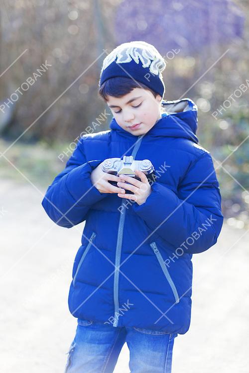 Boy plays with vintage camera