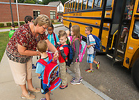 Mrs. Phelps greets and assists students arriving at Elm Street Elementary School Tuesday morning on their first day.  (Karen Bobotas/for the Laconia Daily Sun)
