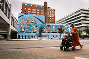 31 AUGUST 2020 - DES MOINES, IOWA: People walk past a mural in downtown Des Moines. Des Moines, like many US cities, is suffering through an extended business slump. Des Moines is home to many insurance and financial services, and those businesses have moved to a work from home model. Downtown businesses, like cafes and convenience stores and dealing with an unprecedented loss of business.      PHOTO BY JACK KURTZ