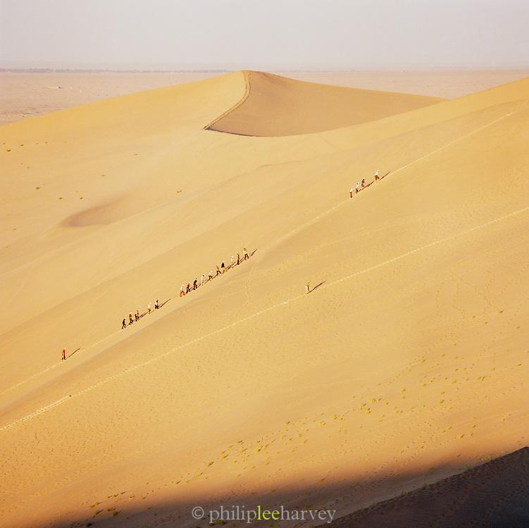 Tourists climb the steep sand dunes, Silk Route; Dunhuang, Jiuquan, Gansu Province, China.