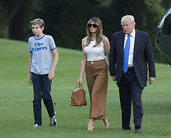 June 11, 2017 - Washington, District of Columbia, U.S. - President DONALD TRUMP and First Lady MELANIA TRUMP hold hands as they walk across the South Lawn as they and their son BARRON TRUMP wearing 'The Expert' shirt, left, return to the White House in Washington, DC, after a trip to New Jersey. (Credit Image: © Chris Kleponis/CNP via ZUMA Wire)