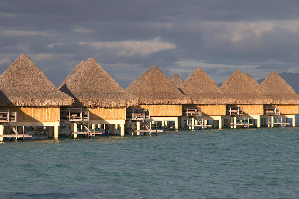 Overwater bungalows in a row at sunset, Bora Bora, Society Islands, South Pacific