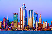 New York skyline glows at dusk, featuring the skyscrapers of Hudson Yards, the West Side of Manhattan and the Hudson River, New York City.