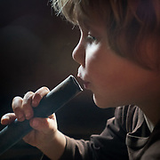 A child blowing on fire with a pipe.