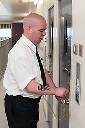 Prison officer locking a cell door, HMP Bronzefield, women's prison in Surrey