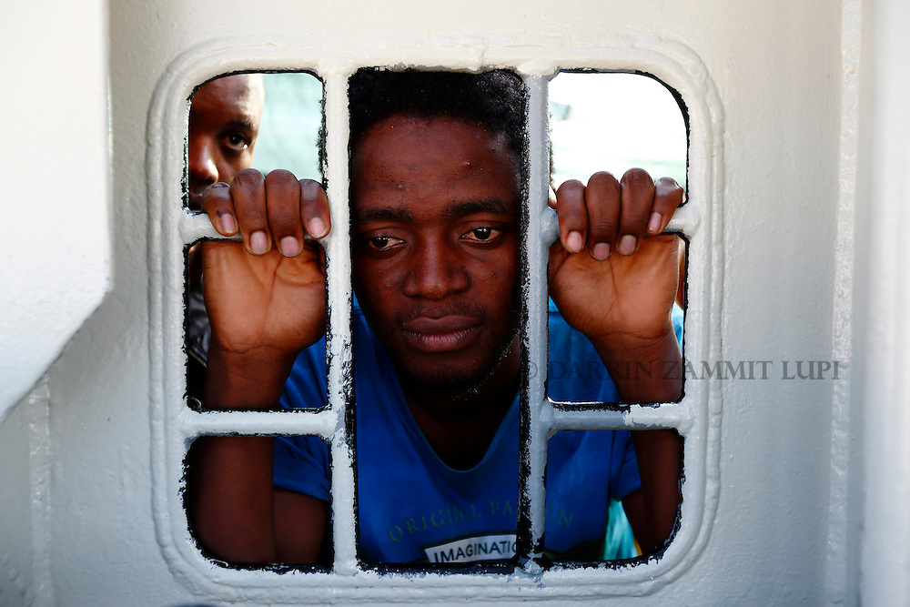Migrants look out of a window on the Medecins san Frontiere (MSF) rescue ship Bourbon Argos as it arrives in Trapani, on the island of Sicily, Italy, August 9, 2015.  Some 241 mostly West African migrants on the ship arrived on the Italian island of Sicily on Sunday morning, according to MSF.<br /> REUTERS/Darrin Zammit Lupi <br /> MALTA OUT. NO COMMERCIAL OR EDITORIAL SALES IN MALTA