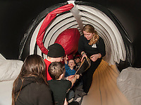 Abby Gronberg (standing on right) shows Theresa Vintinner, Aiden Vintenner and Mike Daoust a baleen (mouth) as Carter Bullerwell notices the whale's blowhole during their visit inside the belly of a whale during Blue Ocean Society for Marine Conservation's whale presentation on Sunday afternoon at the Leavitt Park Clubhouse.   (Karen Bobotas/for the Laconia Daily Sun)