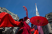 A woman, called Red Sarah dances in front of a pink yacht parked in the middle of Oxford Circus during a protest against climate change on 15th April, 2019 in London, United Kingdom.  Extinction Rebellion have blocked five central London landmarks in protest against government inaction on climate change.