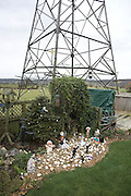 Gnomes and garden figures displayed below an electricity pylon in a back Somerset garden.
