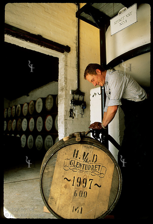 Worker fills cask with new whisky to be aged at least twelve yrs at Glenturret Distillery; Crieff Scotland