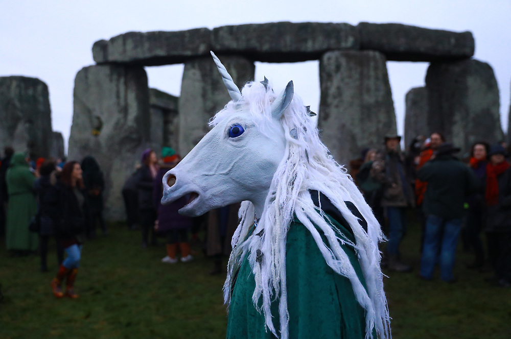A reveller in unicorn costume takes part in winter solstice celebrations at the ancient Stonehenge monument in Wiltshire, Britain, 22 December 2017. The winter solstice, also known as midwinter, marks the day with the shortest period of daylight and the longest night of the year