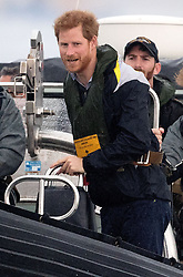 Prince Harry stands in a RIB as he watches sailors participating in a yacht race in Sydney harbour during a day of events to mark the official launch of the Invictus Games Sydney 2018.